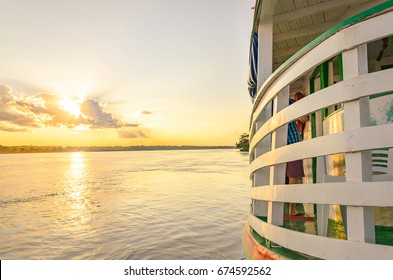 PORTO VELHO, BRAZIL - JUNE 17, 2017: Landscape of a traditional and classic boat ride on Rio Madeira river at sunset. Boats departs from Estrada de Ferro Madeira-Mamore carrying tourists.