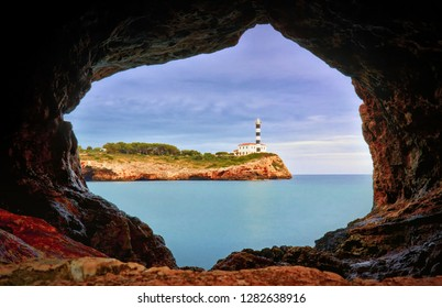 Portocolom lighthouse, stone cave, calm blue sea, Mallorca, Spain.
