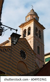 Portofino, 16/03/2017: a street lamp and the bell tower of the 12th century Church of St. Martin, Divo Martino, the striped church dedicated to St. Martin of Tours in the oldest area of the suburb