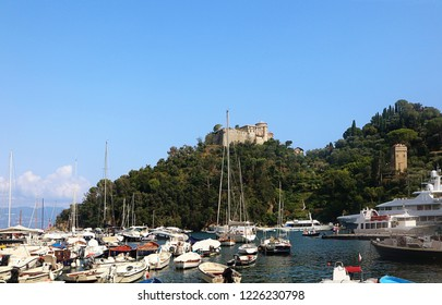 PORTOFINO, ITALY - AUGUST 30, 2018 view  of the medieval Castello Brown, built for harbor defence in 15th century, towering above the Portofino bay and the boats moored