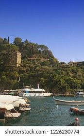 PORTOFINO, ITALY - suggestive view of  Portofino harbor with an antique tower among lush Mediterranean vegetation and the boats moored