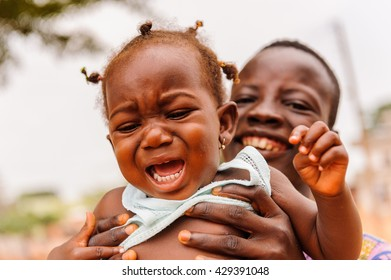 PORTO-NOVO, BENIN - MAR 10, 2012: Unidentified Beninese man hols his little crying girl scared of camera. People of Benin suffer of poverty due to the difficult economic situation