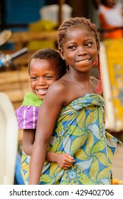 PORTO-NOVO, BENIN - MAR 10, 2012: Unidentified Beninese girl carries her little sister smiling in a colorful dress. People of Benin suffer of poverty due to the difficult economic situation