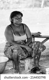 PORTO-NOVO, BENIN - MAR 8, 2012: Unidentified Beninese fat woman works at the market. People of Benin suffer of poverty due to the difficult economic situation.