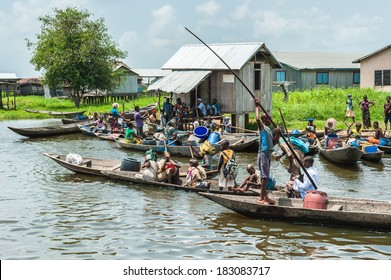 PORTO-NOVO, BENIN - MAR 9, 2012: Unidentified Beninese people in wooden boats. People of Benin suffer of poverty due to the difficult economic situation.