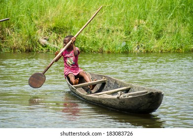 PORTO-NOVO, BENIN - MAR 9, 2012: Unidentified Beninese girl in a pink dress rows a wooden boat. People of Benin suffer of poverty due to the difficult economic situation.