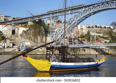 Porto,Portugal - December 28, 2016: Rabelo boat and bridge in Porto. An old portuguese boat on Douro river in front of the Dom Luas I bridge.
