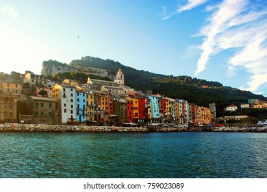 Portovenere: old town, buildings with colored facades, hill and sky with clouds, seen from the boat