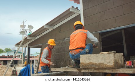 Portoviejo, Manabi / Ecuador - September 1 2018: Bricklayers with a helmet working on plastering with cement a wall of blocks on the outside of a house under construction
