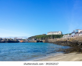 Portpatrick, Dumfries & Galloway, Scotland - July 30, 2015: Portpatrick beach, hotel and harbour in the sunshine as seen from the beach.