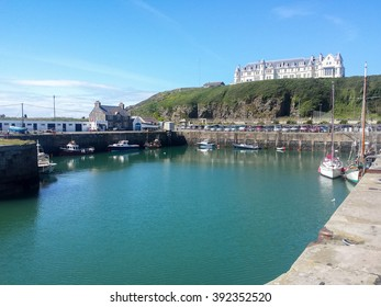 Portpatrick, Dumfries & Galloway, Scotland - July 30, 2015: Portpatrick harbour and hotel in the sunshine as seen from the harbour wall.