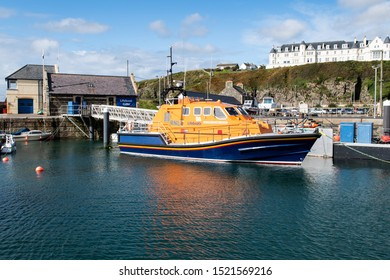 Portpatrick, Scotland, UK - Sep 29th, 2019 - Orange Lifeboat in Portpatrick in Dumfries and Galloway region of Scotland. Harbor and local hotel.