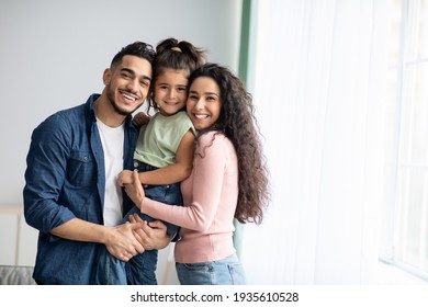 Portraif Of Happy Arabic Parents Posing With Their Little Daughter At Home