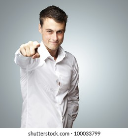 portraiit of a young man pointing with his finger against a grey background