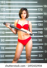 portrail asia sexy girl wear red bikini holding basebll bat with police lineup mugshot background.