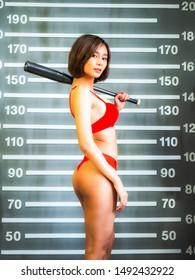 portrail asia sexy girl wear red bikini holding basebll bat with police lineup mugshot background.