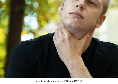 Portrain of young man with sore throat standing in the park and hand touching his Ill neck