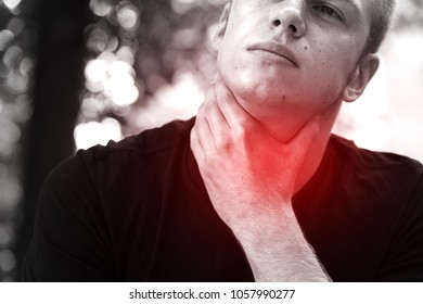 Portrain of young man with sore throat standing in the park and hand touching his Ill neck. Black and white with a red accent