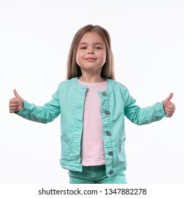 Portrair of beautiful little girl showing thumbs up or Like sign. The portrait is made on a white background. Girl looks into the camera artistically.