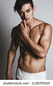 Portrair of a male model with perfect body in white underwear posing over grey background. Close-up. Studio shot.