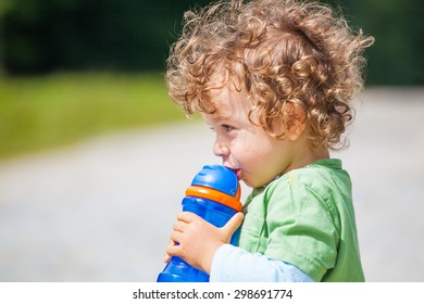 The portrait of a 1 and a half year old baby boy drinking water outdoors.