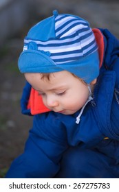 Portrait of 1 year old baby boy playing outside in spring.