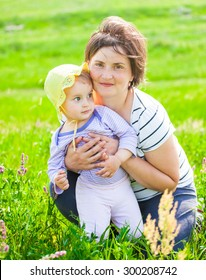 Portrait of 1 year old baby girl with her mother on a meadow.