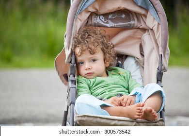 Portrait of 1 year old baby boy in a stroller.