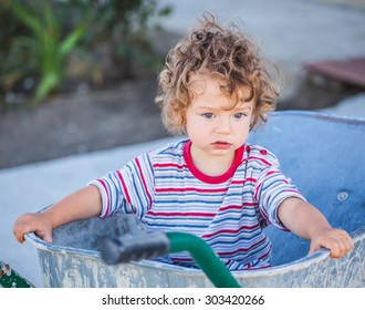 Portrait of 1 year old baby boy playing with a wheel barrow.
