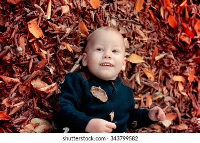 Portrait of 1 year old baby boy relaxing in the woods in the fall.