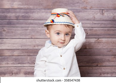 Portrait of a 1 year old baby boy wearing a Romanian traditional hat.