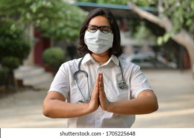 Portrait of 1 young medical health care female worker with hands crossed / folded in namaste, wearing surgical mask to protect herself from Corona Virus (COVID-19) pandemic against blur background