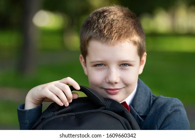Portrait of a 10 year old boy smiling, holding a school backpack. Close-up of a mischievous, funny boy.