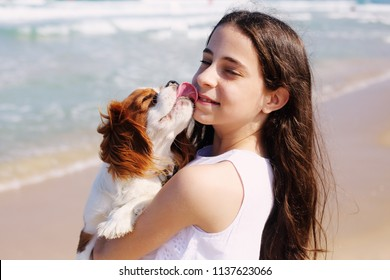 Portrait of  12 years old girl walking with her dog on the beach in summer day