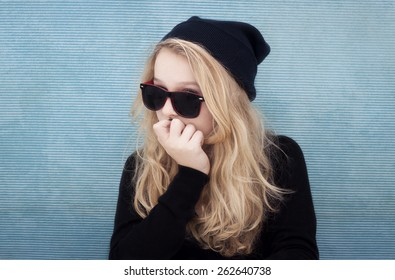 Portrait of 13 year old teenage girl with beenie and glasses. Cheeky, strong, bold, cocky