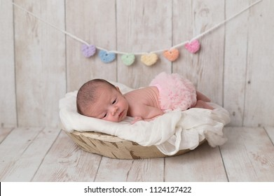 Portrait of a 2 week old newborn baby girl wearing frilly, pink bloomers. She is lying in a wooden bowl and there is a heart garland in the background.
