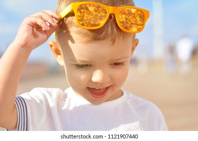 Portrait of a 2 year old smiling boy in bright orange sunglasses with a reflection of the hearts in them