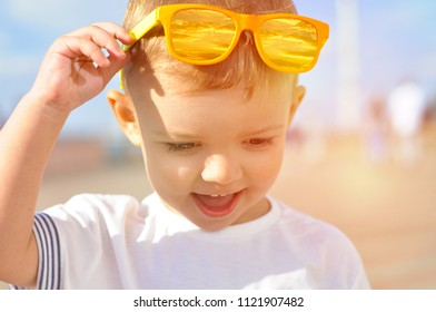Portrait of a 2 year old smiling boy in bright orange sunglasses with a reflection of the sky in them