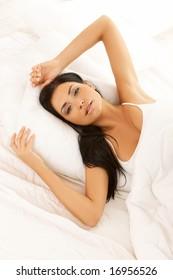Portrait of 20-25 years old beautiful woman on white bed