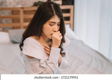 Portrait of 20s young Asian woman having dry cough in bedroom at home