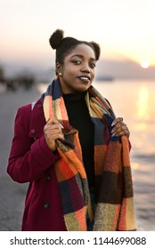 Portrait of a 25 years old African woman with a red coat and weft near to the waters edge with a sunset.