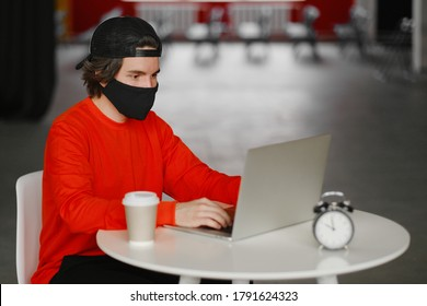 Portrait of a 25-30 year old man wearing a black protective mask, cap and red sweatshirt. The man sits alone at a table in the open space, drinking coffee and working on his laptop. Freelance concept