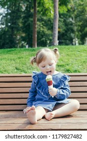 Portrait of a 3 years old girl eating ice cream in a city park on a warm sunny day