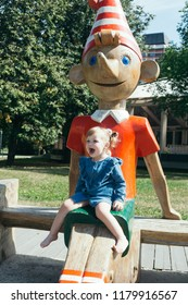 Portrait of a 3 years old girl sitting on a wooden statue of Pinocchio in a city park on a warm sunny day
