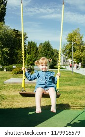 Portrait of a 3 years old girl on a swing on the playground a city park on a warm sunny day