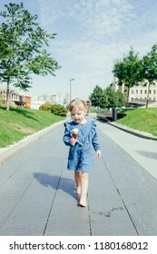 Portrait of a 3 years old girl walking barefoot with ice cream in a city park on a warm sunny day