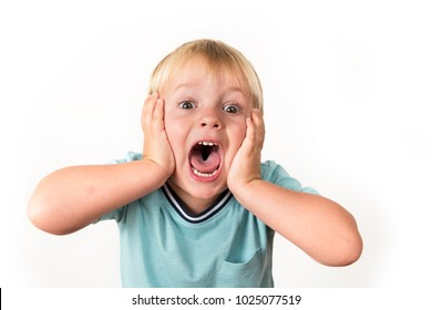 portrait of 3 years old little blond kid with mouth open screaming surprised or scared holding his head with his small hands isolated on white background in facial expression and emotions concept