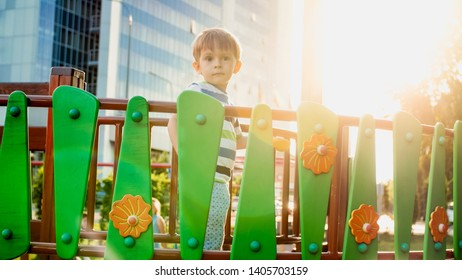 Portrait of 3 years old little boy walking and crawling on wooden bridge on children playground at park. Kids playing and having fun on playground
