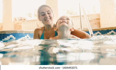 Portrait of 3 years old toddler boy with mother swimming in the indoors pool. Child learning swimming and doing sports. Family enjoying and having fun in water