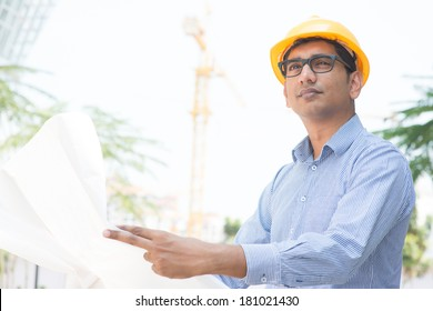 Portrait of a 30s Indian male site contractor engineer with hard hat holding blue print paper at construction site, crane at the background.